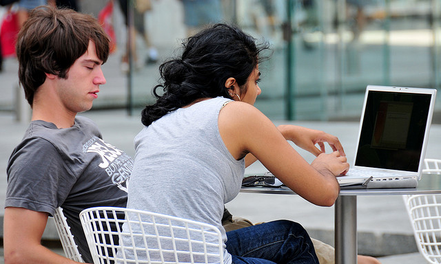 Two people seated outdoors looking at a laptop