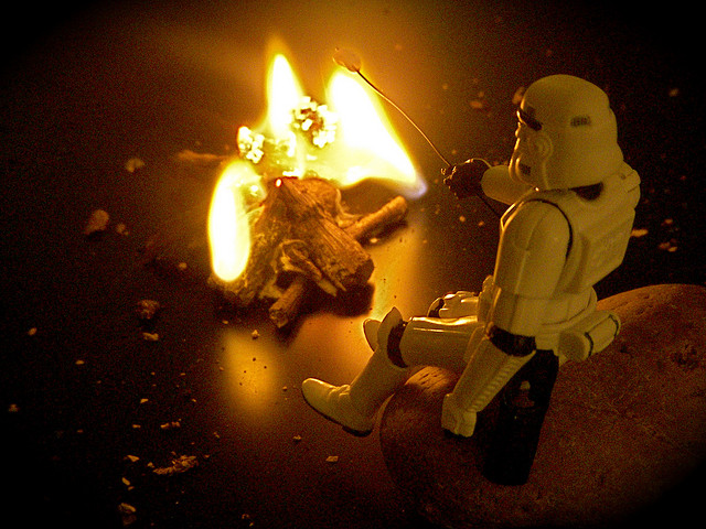 A Storm Trooper doll seated by a fire with a marshmallow on a stick
