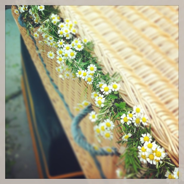 A wicker coffin with flowers protruding from under the lid.