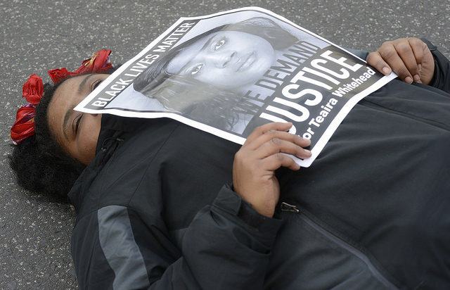 A Black person lying on the ground in a die-in with a sign demanding justice
