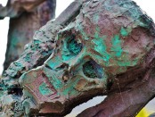 A sculpture of a copper skull covered with patina