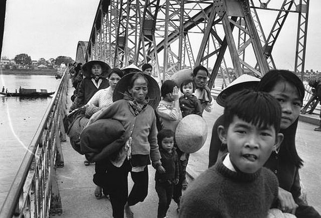 Vietnamese refugees walking across a bridge