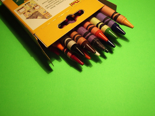A box of crayons on a bright green surface
