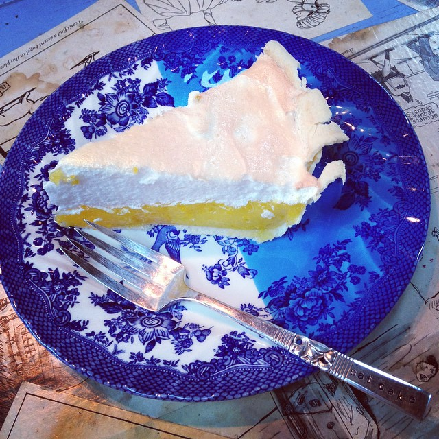 A slice of lemon meringue pie on a china plate