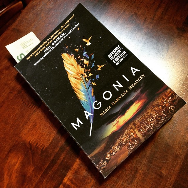The cover of MAGONIA featuring a feather exploding into birds high up over a city