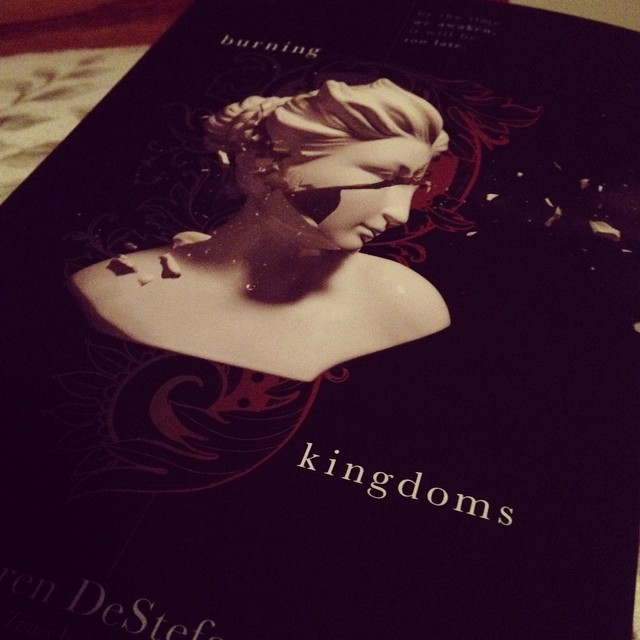 A shattered statue on the cover of BURNING KINGDOMS by Lauren DeStefano
