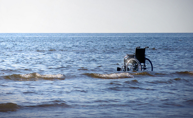 A wheelchair sitting in breaking waves