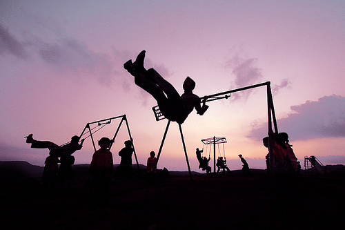 Kids on swingsets at sunset.