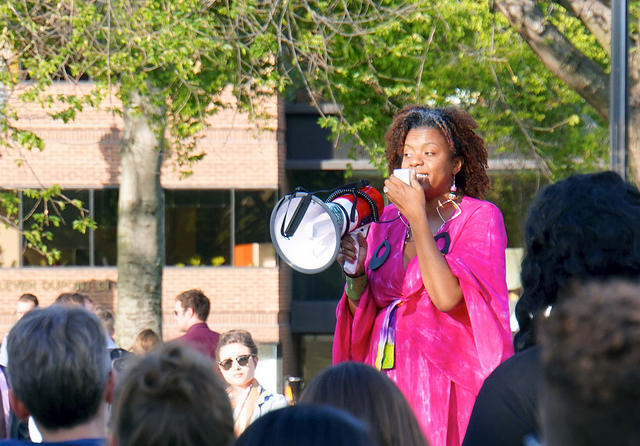 A person speaking at a vigil and rally