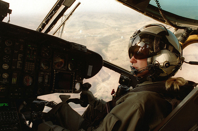 A ponytailed blonde pilot in the seat of a helicopter