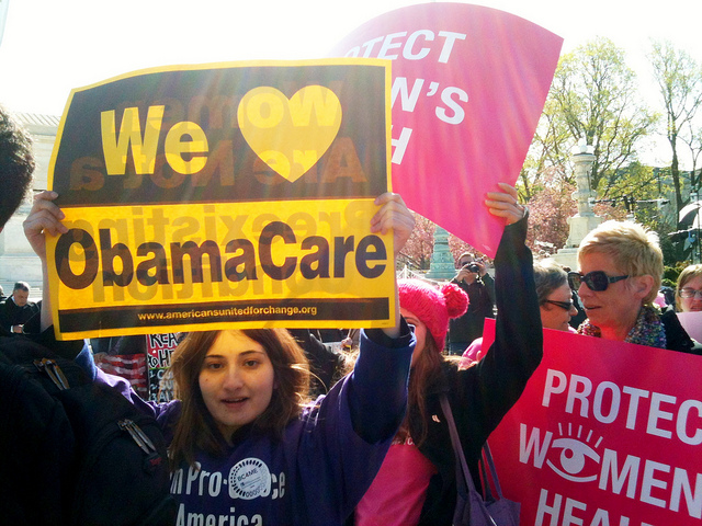 People holding up signs at a pro-Obamacare rally
