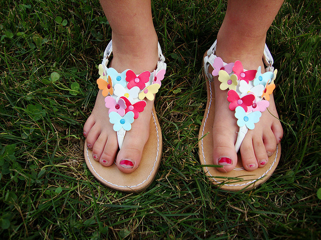 A pair of feet in flowered sandals.