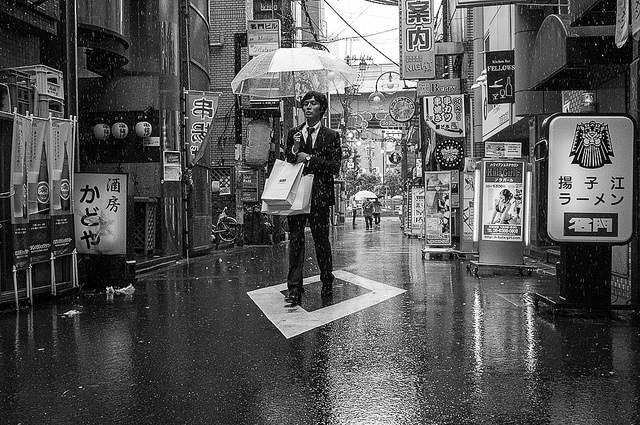 A person under an umbrella in a Japanese street