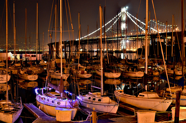A boat bedecked in lights docked at Treasure Island with the new span of the Bay Bridge behind it.