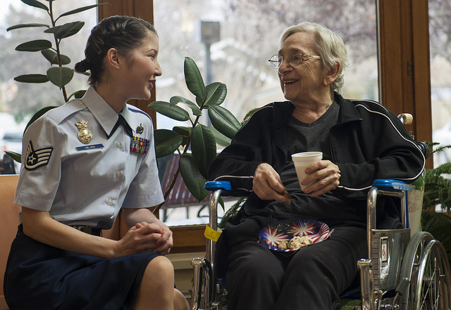 A member of the Air Force visits a veteran in a nursing facility