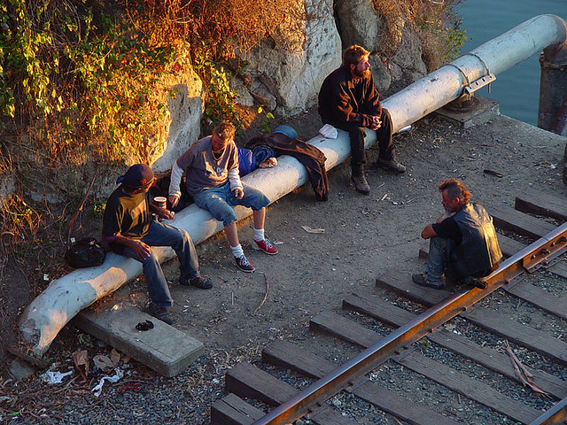 A group of homeless people sitting by railroad tracks in the sun.