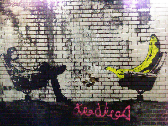 Graffiti art featuring a banana talking to a person leaning back in a chair