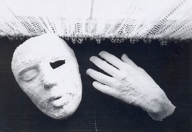 A black and white photo of a plaster cast mask and hand.