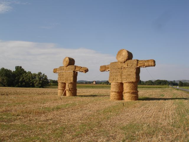 Two massive human figures made of straw