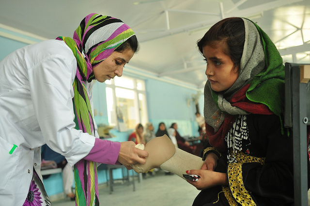 An amputee being assisted with a prosthetic