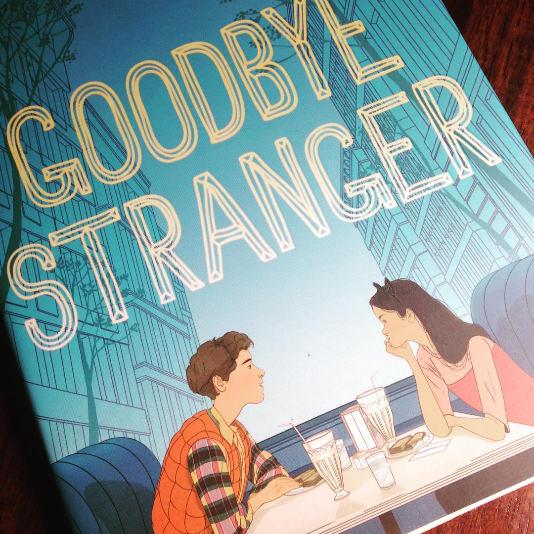 Two youth leaning across a table at each other on the cover of GOODBYE STRANGER