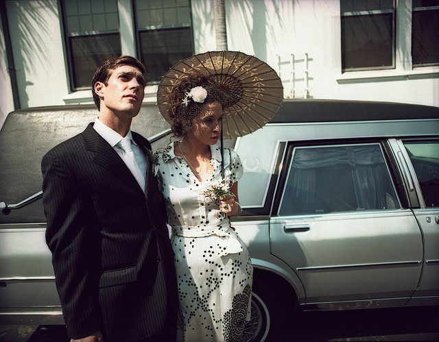 Two people posing in front of a hearse.