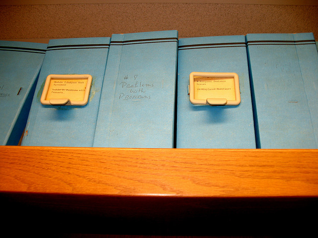 Boxes on a shelf, one of which is labeled PROBLEM WITH PRONOUNS.