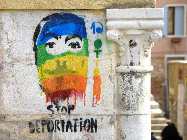 Rainbow graffiti exhorting the viewer to STOP DEPORTATION