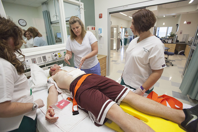 An actor lies on a backboard simulating shooting injuries while medical staff evaluate him.