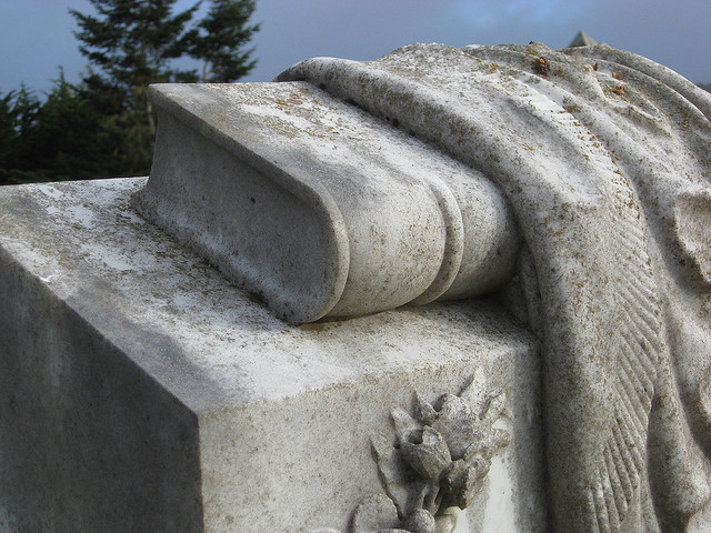 A carved book and drape on the top of a headstone