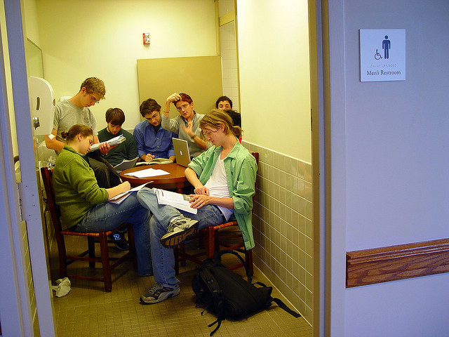 A group of students crammed into a bathroom, studying at a desk.