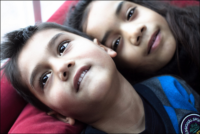 Two children smiling up at the camera.