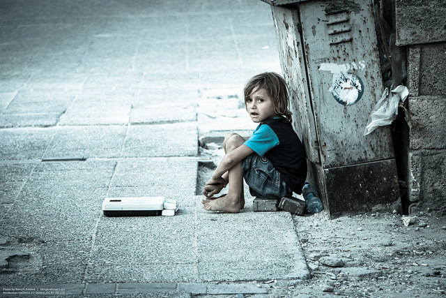 A small child sitting on a sidewalk.