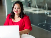 A woman of colour seated at a computer.