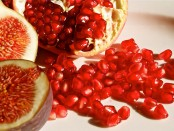 A pomegranate and a fig both sliced open to reveal their red insides