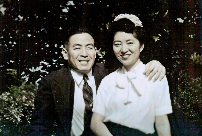 A Japanese couple in Western clothes, smiling in a pose for the camera.