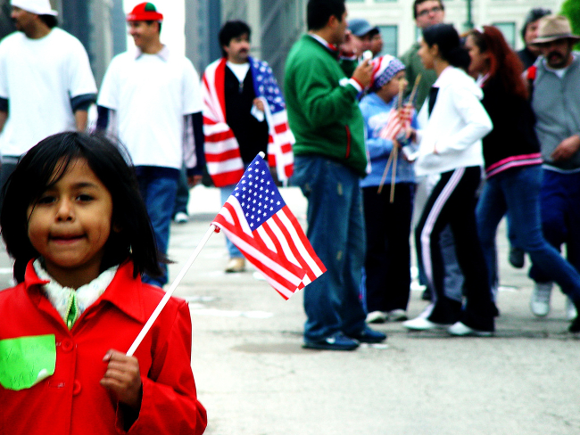 A young person waving a US flag at an immigration rally.