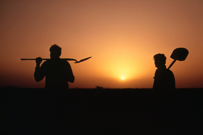 Two labourers silhouetted against the sunset.