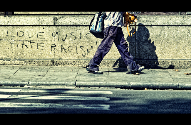 A pedestrian strolls past graffiti enjoining the reader to LOVE MUSIC HATE RACISM