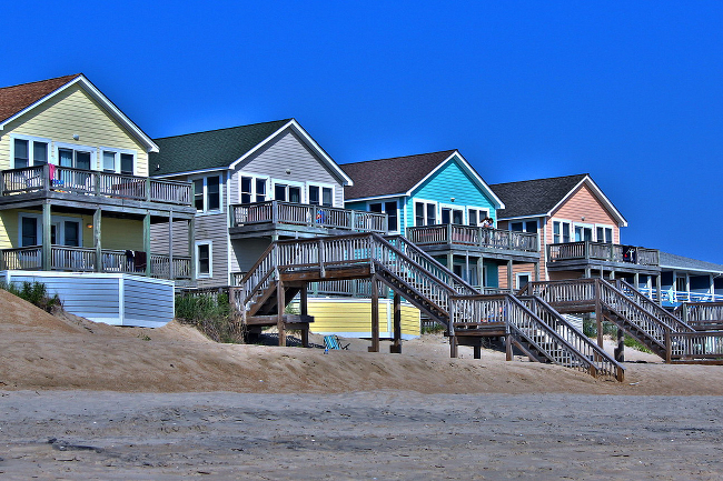Four brightly-coloured beach houses.