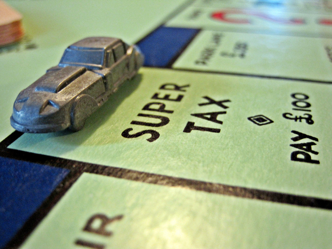 A playing piece on a Monopoly board occupying the Super Tax spot.