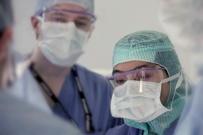 A fully masked surgeon concentrating on the surgical field.