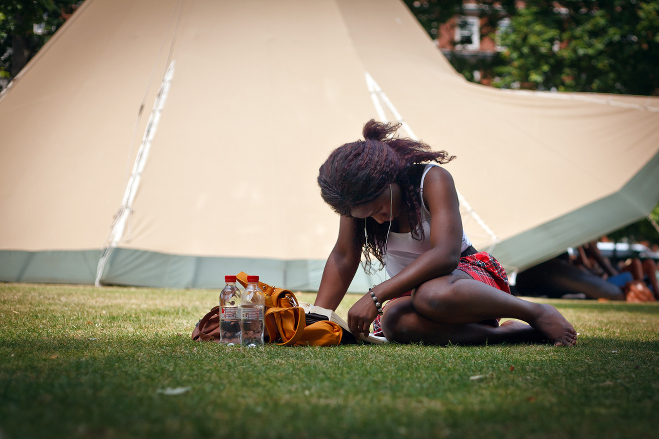A dark-skinned person reading in the sun.