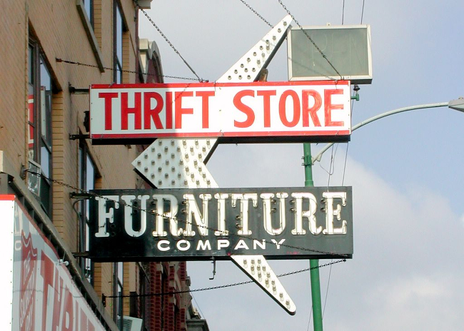 A sign advertising a thrift store and furniture mart.