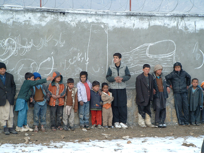Refugees lining up against a wall.
