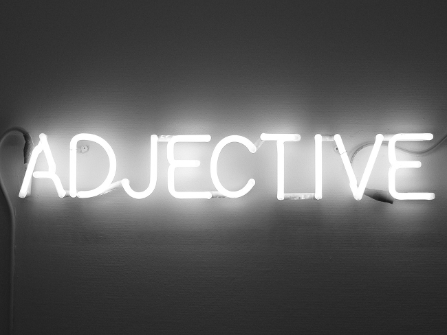 A neon sign reading ADJECTIVE.