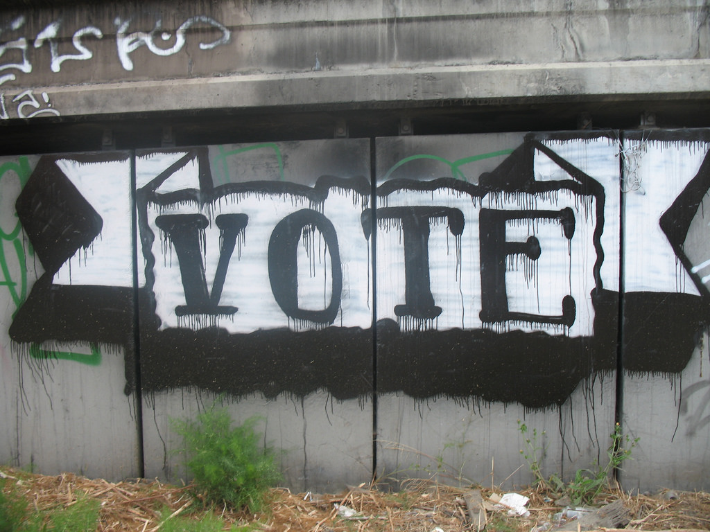 A scrawled graffiti message inviting the observer to vote.