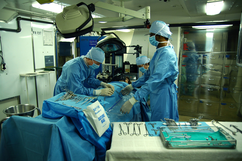 A surgeon and team busily gathered around a patient.
