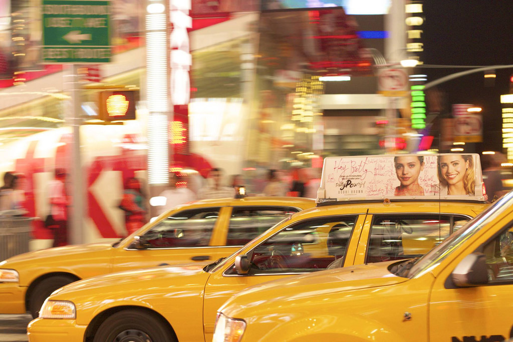 Cabs rushing by on a busy New York street.