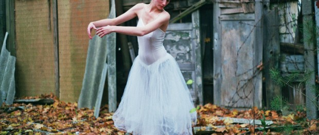 A woman in a ballet costume dancing in front of a shack.